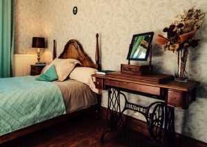 Un miroir amovible ancien posé sur une table intégrant une machine à couture Singer