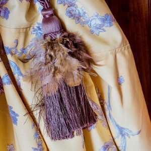 Une embrasse en plume orne le rideau orné de cornes d'abondance